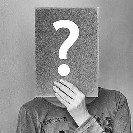 Person hält Papier mit Fragezeichen vor Gesicht