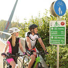 zwei Radfahrer begutachten ein Schilt an der Traunbrücke (Trodat)