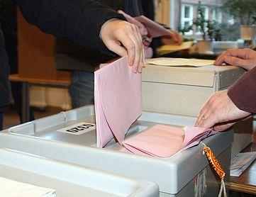Kuvert einer Wahl wird in die Wahlurne gesteckt.
