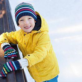 Eishalle - fröhlicher Junge in gelber Jacke am Eis