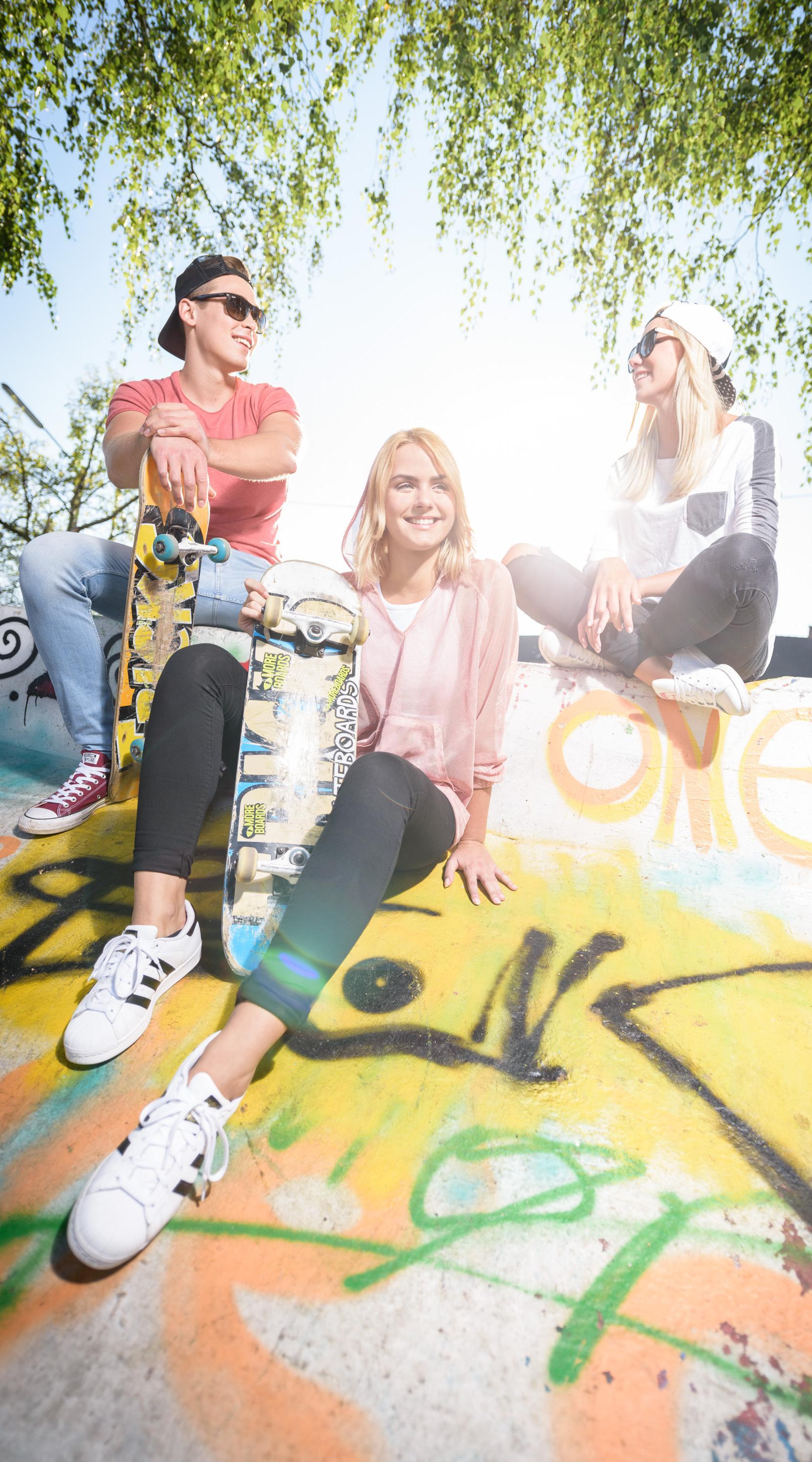 Jugendliche draußen mit Skateboard auf Skateboardrampe