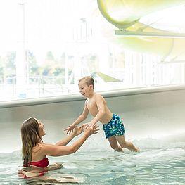 Mutter und Kind im Badespaß bei der Rutsche im Freibad