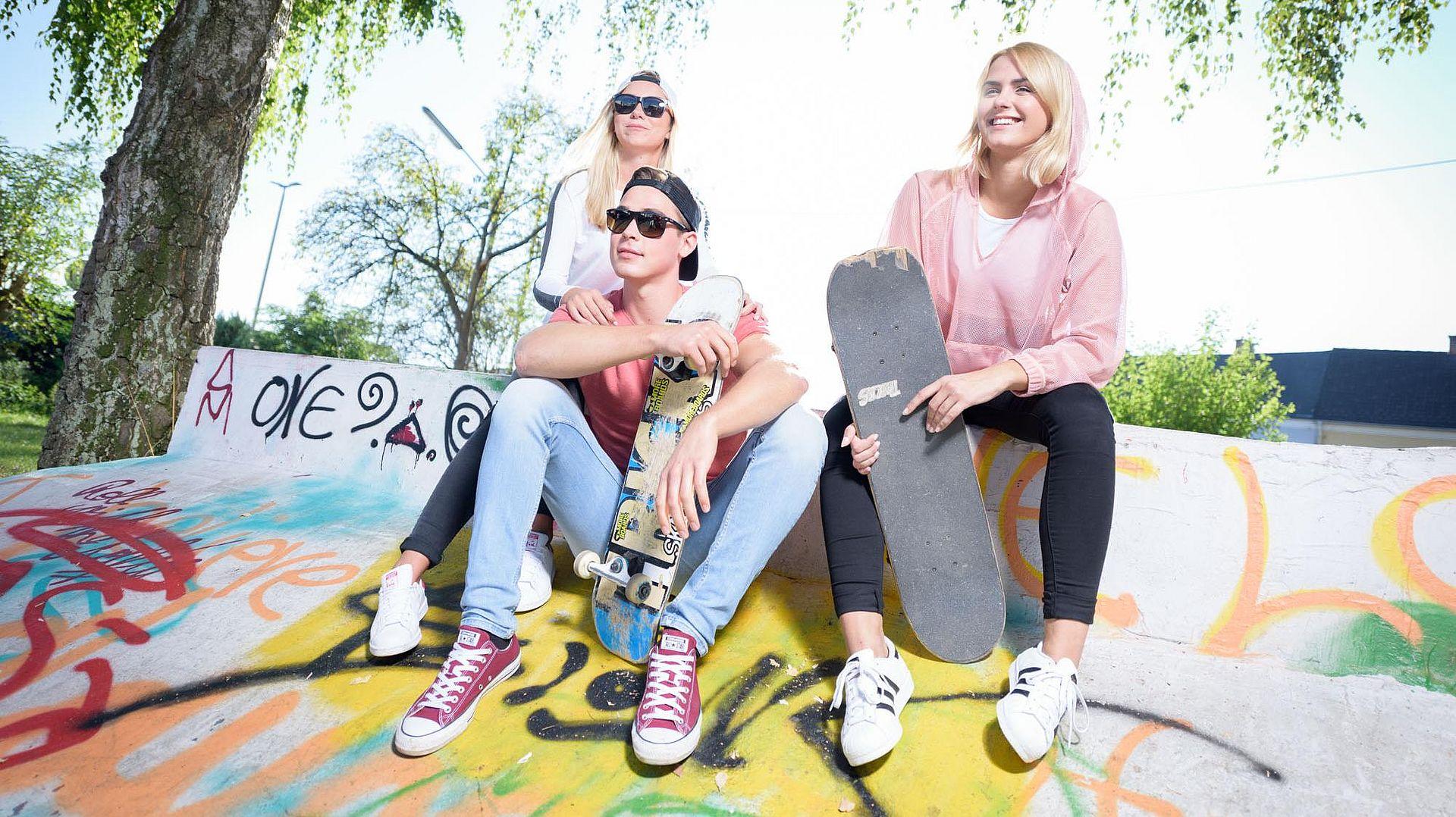 Jugendliche draußen mit Skateboard auf einer Skateboardrampe
