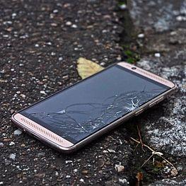Handy mit kaputtem Display am Boden