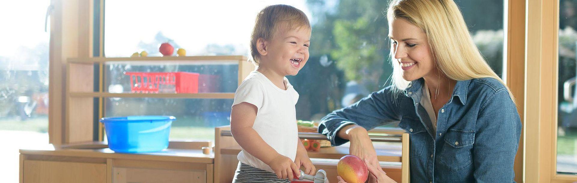 Mutter und lächelndes Kind in der Spielküche