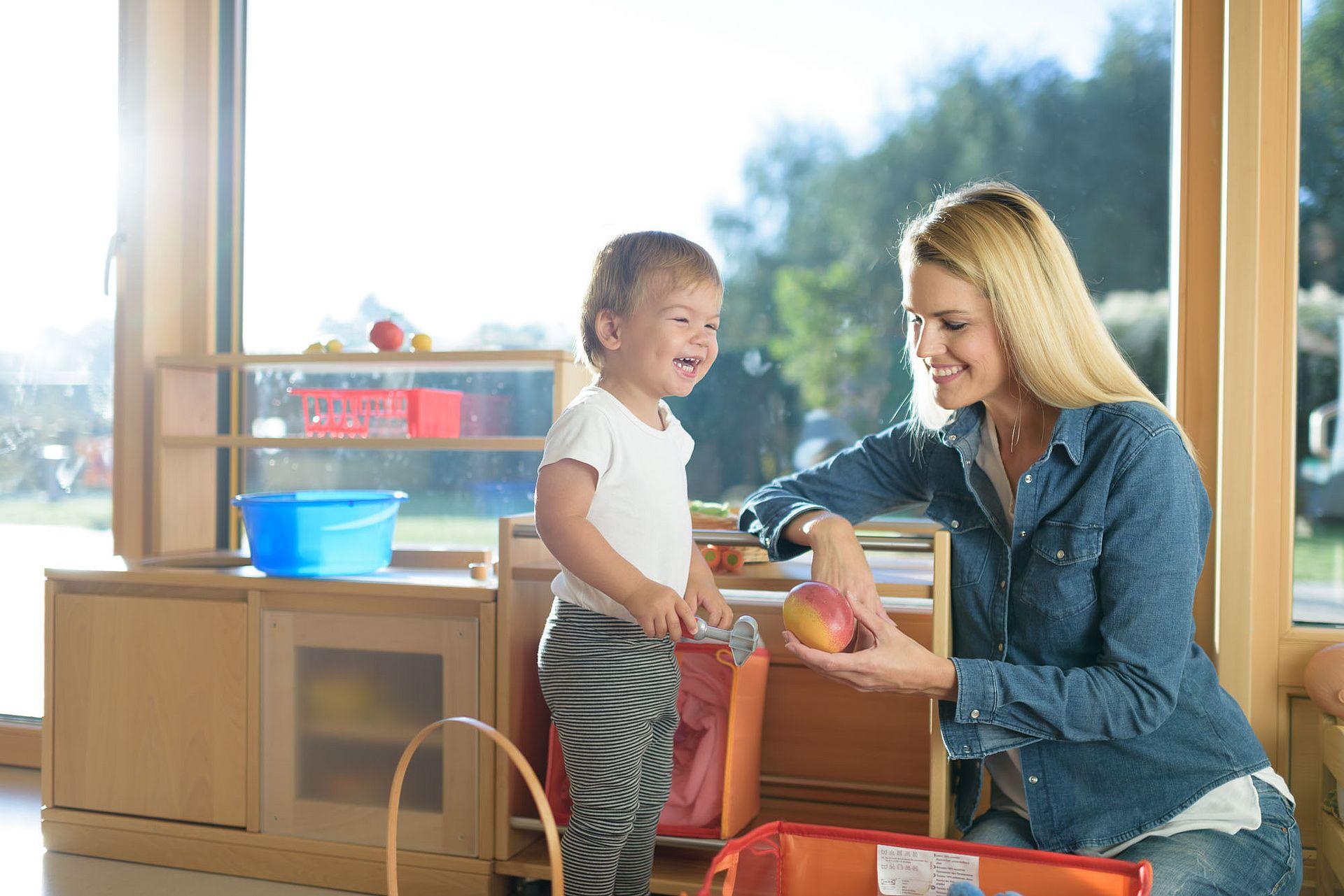Mama mit lächelndem Kind in der Spielküche